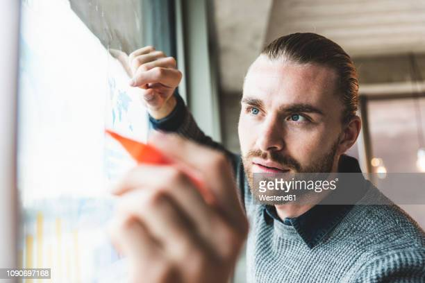 young businessman working on data at windowpane - innovation stock-fotos und bilder