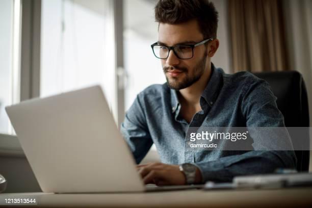 jonge zakenman die aan laptop werkt - one young man only stockfoto's en -beelden
