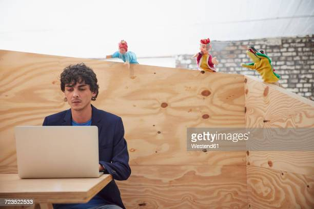Young businessman working on laptop with hand puppets watching him from wooden wall