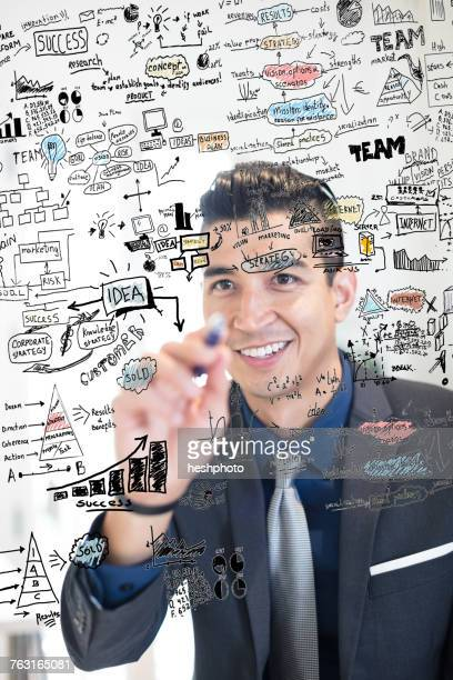 young businessman writing ideas on glass wall in creative office - heshphoto stock pictures, royalty-free photos & images