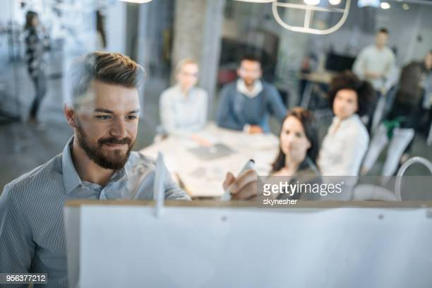 young businessman writing ideas on whiteboard during a meeting with his colleagues. - business meeting stock pictures, royalty-free photos & images