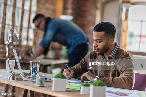 Young businessman writing notes in the office