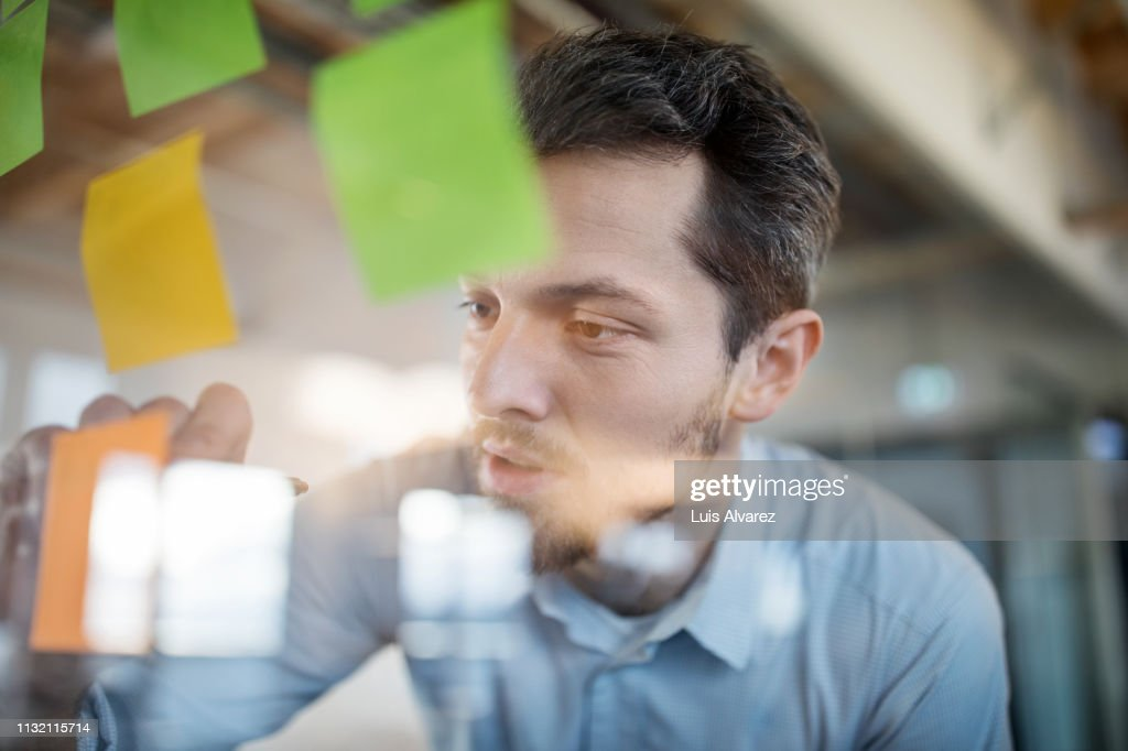 Young businessman writing on adhesive note : Stock-Foto