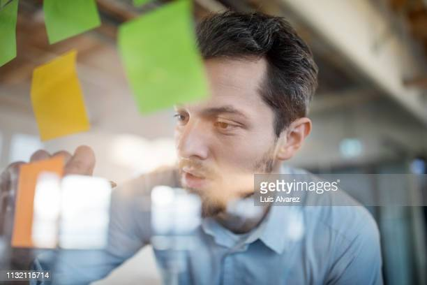 young businessman writing on adhesive note - vision stock-fotos und bilder