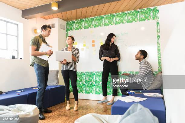 young businessmen and women having discussions in creative meeting room - heshphoto stock pictures, royalty-free photos & images