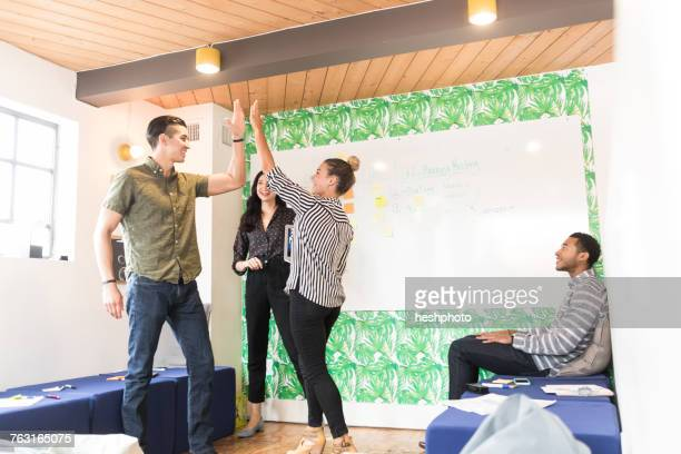 young businessmen and women high fiving in creative meeting room - heshphoto stock pictures, royalty-free photos & images