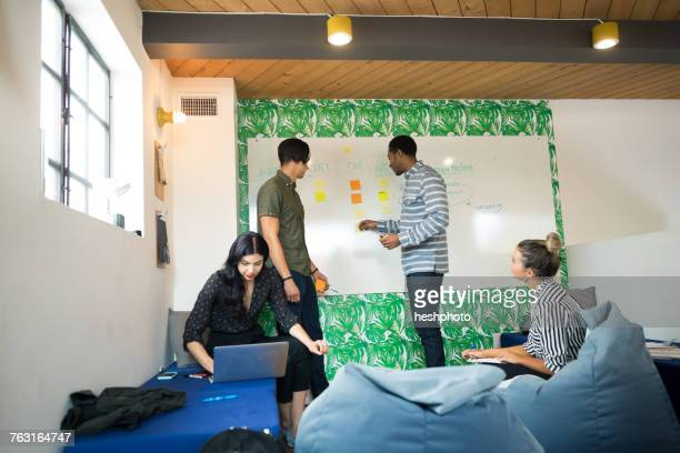 young businessmen and women using laptop and whiteboard in creative meeting room - heshphoto stock pictures, royalty-free photos & images