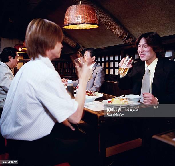 Young businessmen having dinner in restaurant