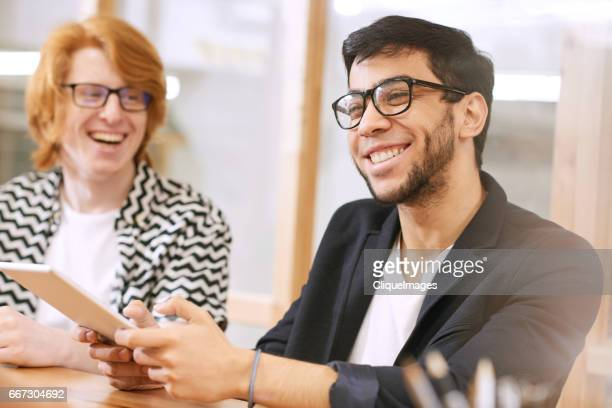 young businessmen having friendly conversation - cliqueimages stock pictures, royalty-free photos & images