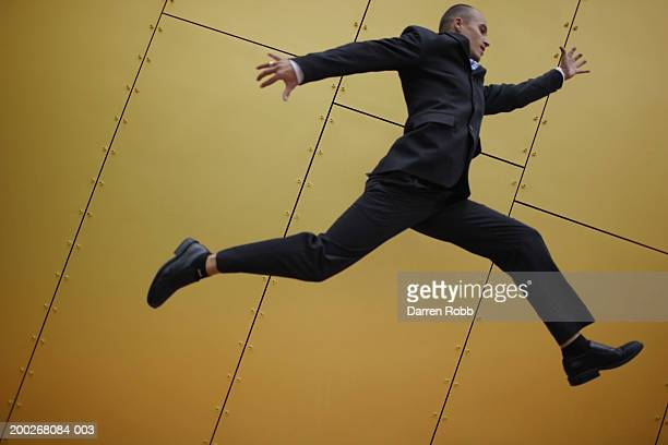 Young businessmen leaping, side view