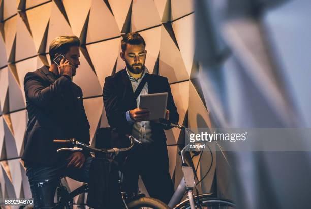 Jungunternehmer auf Fahrrädern mit tragbaren Geräten