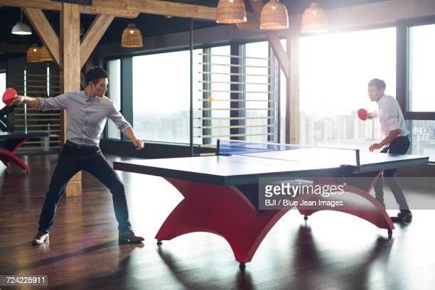 Young businessmen playing ping pong