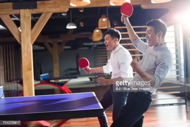 young businessmen playing ping pong - face off sports play stock photos and pictures