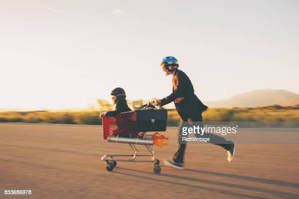 young businessmen racing rocket shopping cart - turnover sport stock photos and pictures