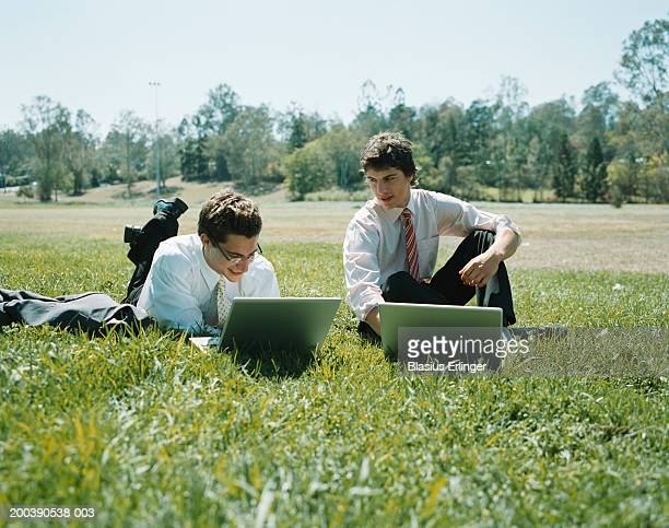 young businessmen using laptops in meadow - blasius erlinger stock pictures, royalty-free photos & images