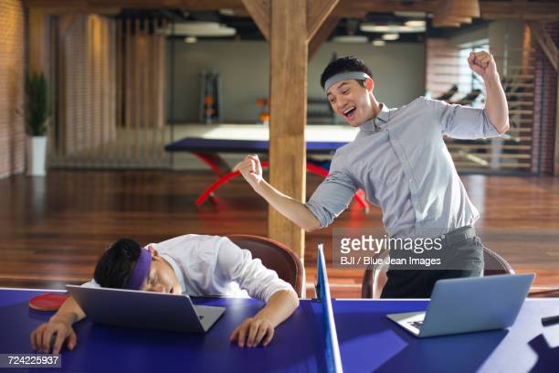 young businessmen using laptops on table tennis table - funny ping pong stock pictures, royalty-free photos & images