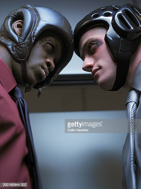 Young businessmen wearing protective head gear, staring at one another