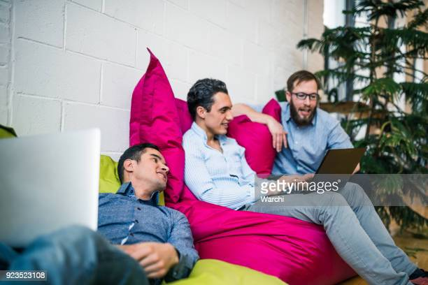 Young businessmen working relaxed on bean bags