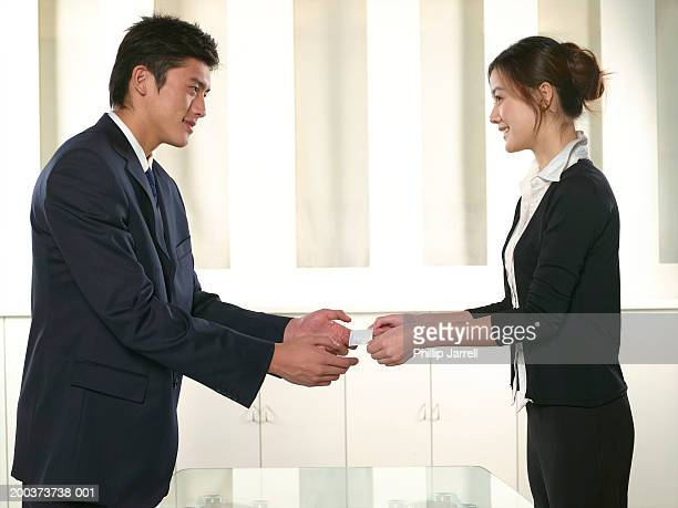 Young businesspeople exchanging card, side view