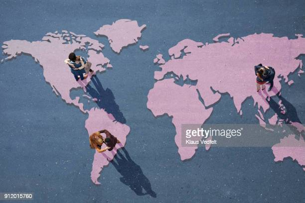 young businesspeople hugging, while standing on world map, painted on asphalt - global village stock pictures, royalty-free photos & images