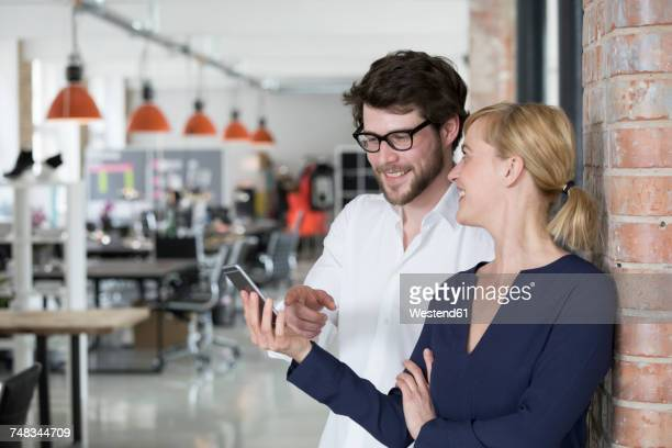 Young businesspeople in their new office looking at smartphone