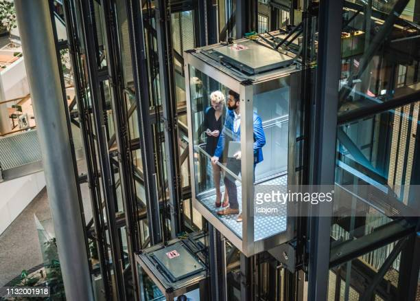 young businesspeople talking in elevator. - picking up stock pictures, royalty-free photos & images
