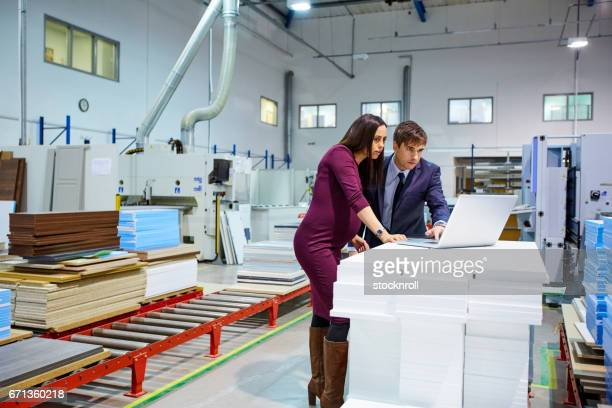 Young businesspeople using laptop on factory shopfloor