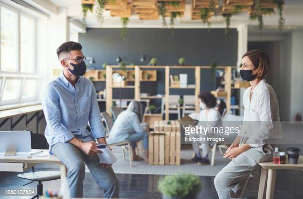 young businesspeople with face mask working in coworking office, talking. - distant stock pictures, royalty-free photos & images