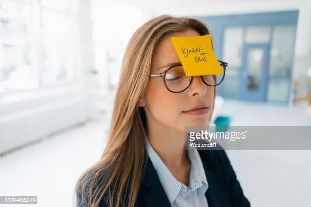 young businesswman with yellow sticky note on her forehead - esgotamento psicológico imagens e fotografias de stock