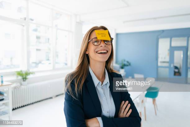 young businesswman with yellow sticky note on her forehead, saying 'burnout' - forehead stock pictures, royalty-free photos & images
