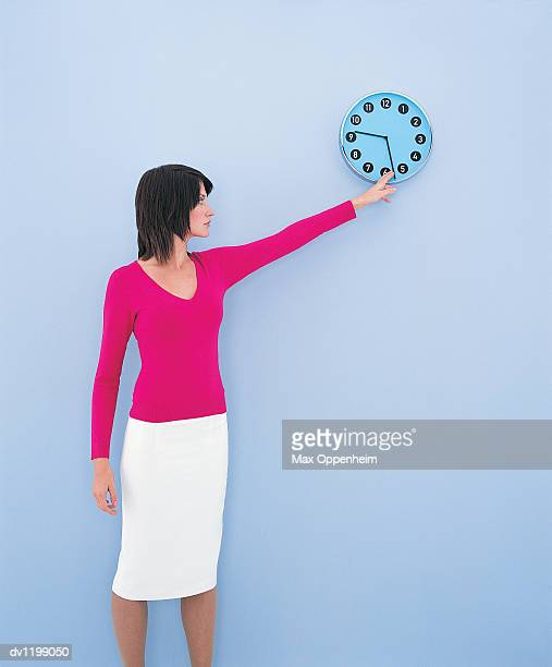Young Businesswoman Adjusting the Minute Hand on a Wall Clock
