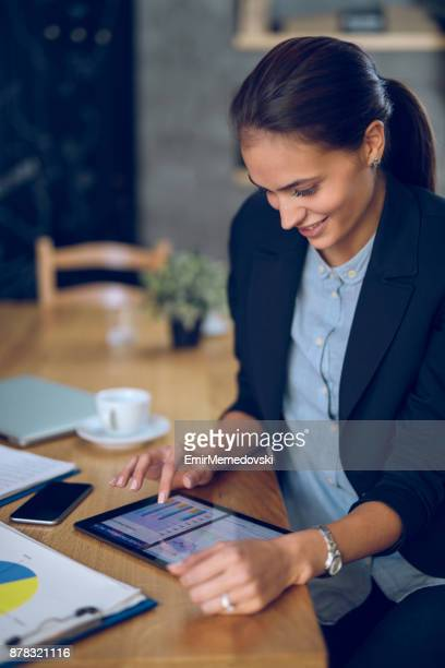 Young businesswoman analyzing business report using digital tablet