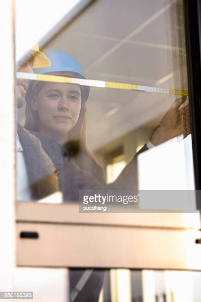 Young businesswoman and architect measuring window in new office