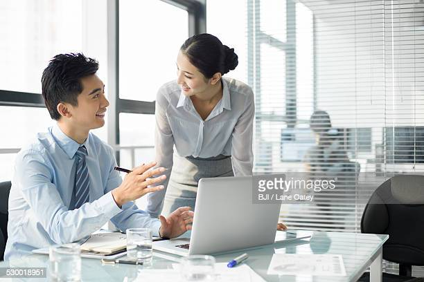 Young businesswoman and businessman talking in office