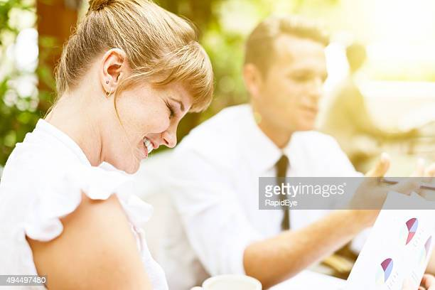 Young businesswoman and male colleague  enjoying breakfast meeting at cafe