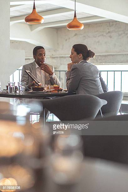 Young businesswoman and man having a business conversation at restaurant