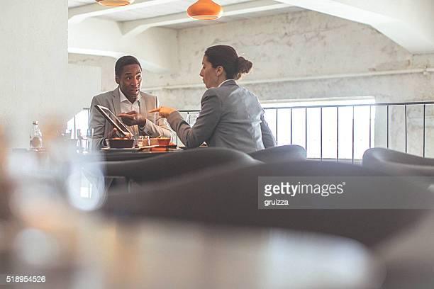 Jeune femme d'affaires et homme d'affaires ayant une conversation au restaurant