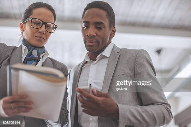 Young businesswoman and man having a conversation in modern office