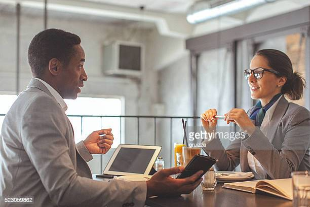Young businesswoman and man having a conversation in restaurant