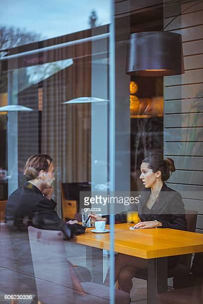 Joven empresaria y hombre teniendo una conversación en un moderno espacio de oficina