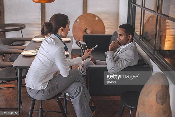 Young businesswoman and man having conversation in modern office space