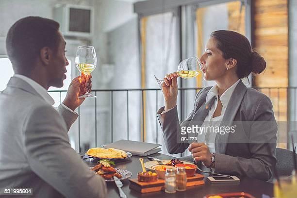Jeune femme d'affaires et homme d'affaires portant un toast au déjeuner au restaurant