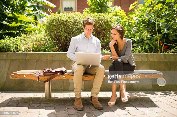 Young businesswoman and man using laptop on bench, London, UK