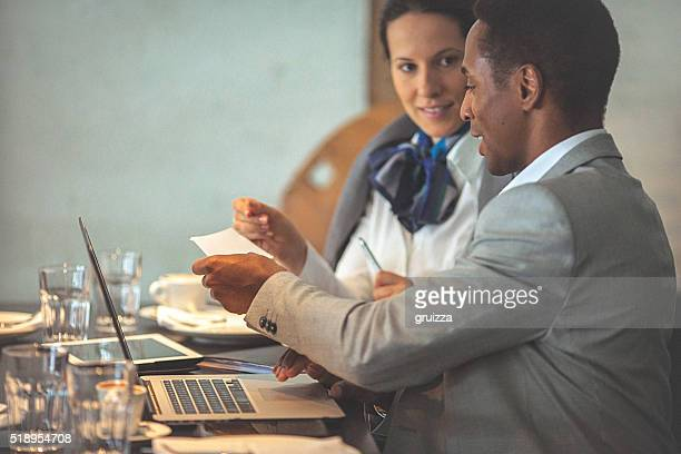 Young businesswoman and man working on a laptop at cafe