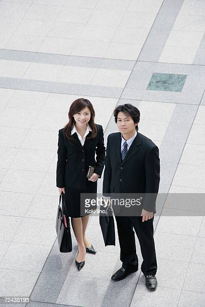 A young businesswoman and mid adult businessman standing