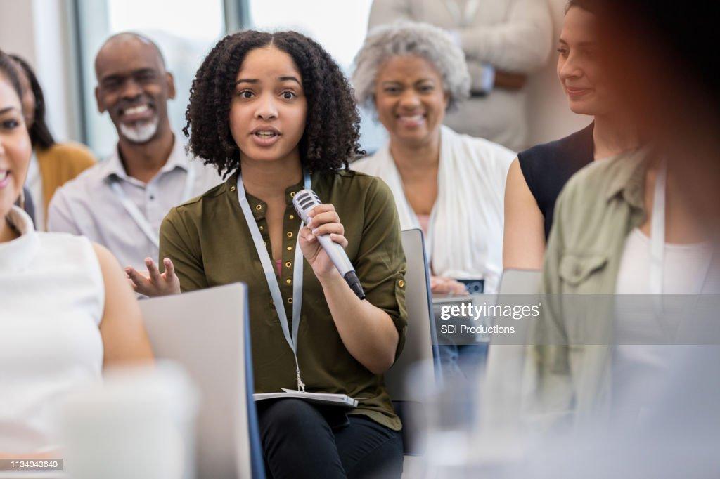 A mulher de negócios nova pergunta durante o seminário : Foto de stock