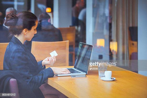 Young businesswoman at cafe using credit card for online transaction