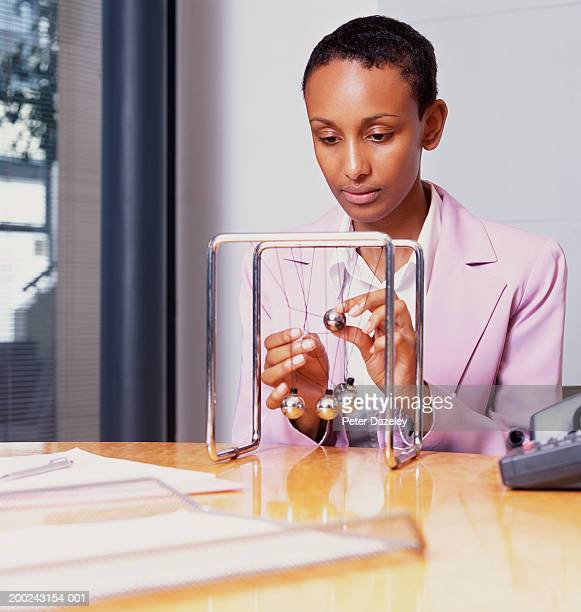 young businesswoman at desk untangling newton's cradle - desk toy stock photos and pictures