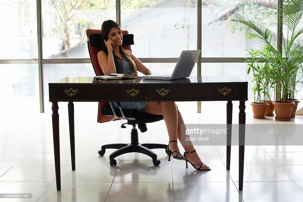 Young businesswoman at desk using mobile phone : Stock Photo