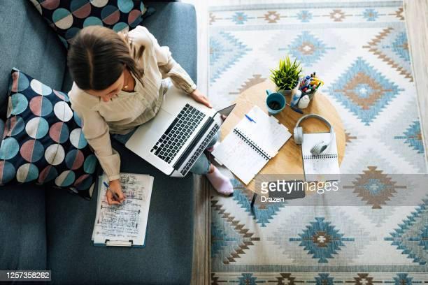 junge geschäftsfrau zu hause mit videoanruf und telearbeit - weitwinkelaufnahme stock-fotos und bilder